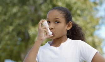 Young girl using inhaler.
