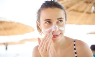 Teenage girl putting suncreen on face.