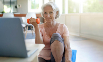Older female sitting on yoga mat, with holing a light weight in one hand, watching laptop.