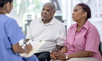 Two elderly individuals talking to a doctor or nurse practitioner