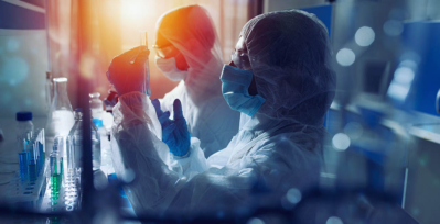 Two people in full protective gear in a lab setting, looking at test tubes.