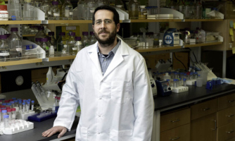 Headshot of researcher Jason McLellan, Ph.D. in lab coat in front of science equipment